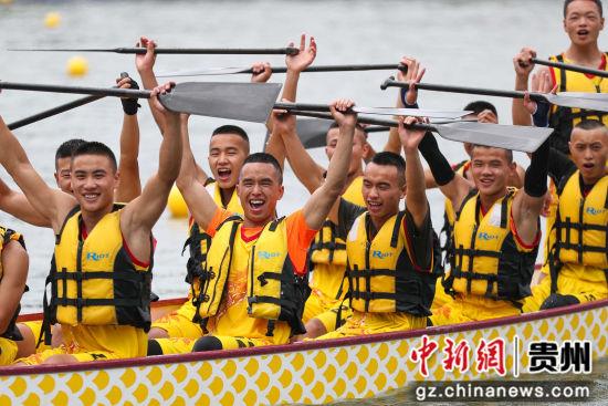 图为冲过终点后,划手举船桨庆祝。