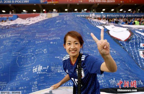 一名日本球迷与巨型大空翼海报合影。