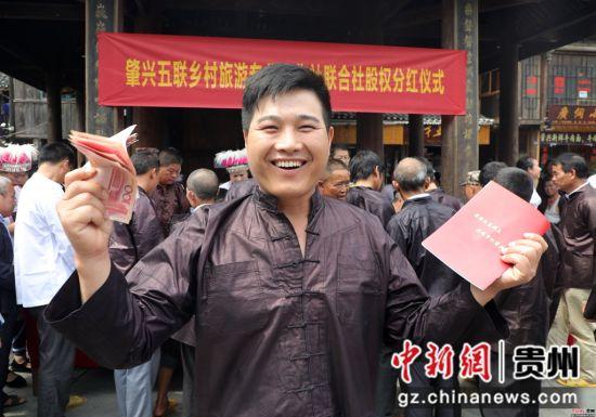 2018年07月13日,在贵州省黎平县肇兴侗寨,侗族村民高兴地展示领到的景区门票分红款和房屋人口股权证。杨代富 摄