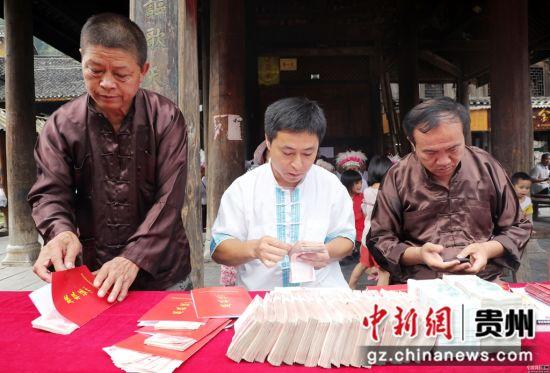 2018年07月13日,在贵州省黎平县肇兴侗寨,合作社工作人员在准备侗族村民的景区门票分红款和房屋人口股权证。杨代富 摄