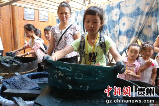 小游客在黎平侗品源体验馆体验用蓝靛水染自己的蜡画作品。 杨代富 摄