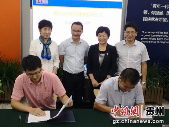 图为雷山县中等职业学校文贵华校长与北京百年职校文博校长进行两校合作的签字仪式
