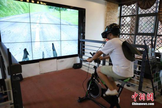 7月23日,游客体验VR自行车骑行。茅台驿站是赤水河谷旅游公路的起点驿站,位于贵州省仁怀市茅台镇。驿站依靠智慧旅游管理平台,在河谷服务大厅建立全息三维电子旅游地图展示系统,游客可以通过运用3D成像技术,以地图展现形式对赤水河谷旅游公路沿途驿站、主要旅游景点进行虚拟展示。据了解,赤水河谷旅游公路是由红色橡胶沥青铺设的自行车道,全长160公里。中新社发 瞿宏伦 摄
