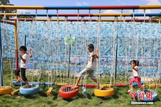 """孩童在湄潭县湄江街道金花村""""七彩部落""""游玩。 瞿宏伦 摄"""