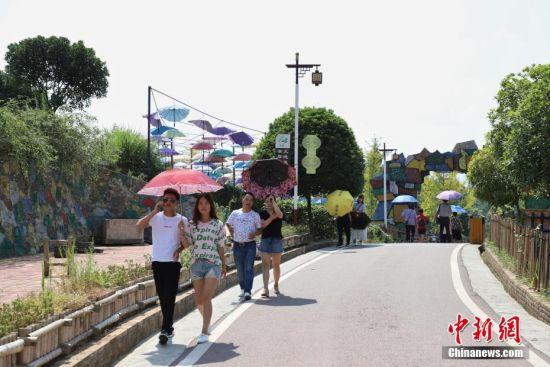 """游客行走在湄潭县湄江街道金花村""""七彩部落""""的乡间小道上。 瞿宏伦 摄"""