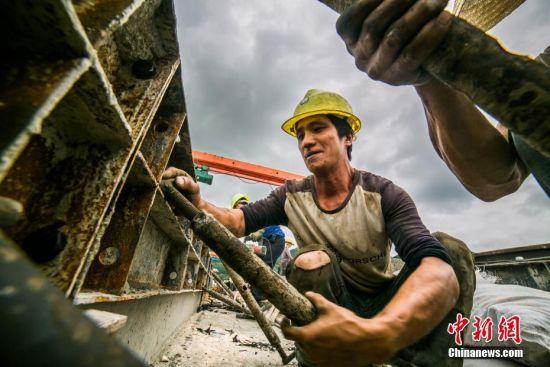 7月27日,贵州大方县东关乡成贵高铁大方站施工现场,铁路施工人员抢抓时间紧张施工。中新社发 罗大富 摄