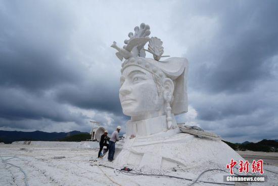 7月31日,两名工人在对奢香夫人头像进行雕刻。奢香夫人的形象是根据贵州宣慰府描绘的奢香夫人通用形象塑造,整座雕塑高49米,工期为三年。头像石雕位于贵州省大方县百纳乡新华村,由大理石雕刻而成,目前已基本完成高达12米的头部雕刻。 中新社记者 贺俊怡 摄
