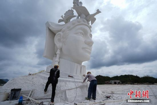 7月31日,两名工人对奢香夫人头像进行雕刻。奢香夫人的形象是根据贵州宣慰府描绘的奢香夫人通用形象塑造,整座雕塑高49米,工期为三年。头像石雕位于贵州省大方县百纳乡新华村,由大理石雕刻而成,目前已基本完成高达12米的头部雕刻。 中新社记者 贺俊怡 摄