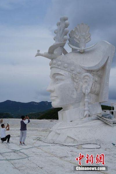 7月31日,两名游客用手机拍摄奢香夫人头像石雕。奢香夫人的形象是根据贵州宣慰府描绘的奢香夫人通用形象塑造,整座雕塑高49米,工期为三年。头像石雕位于贵州省大方县百纳乡新华村,由大理石雕刻而成,目前已基本完成高达12米的头部雕刻。 中新社记者 贺俊怡 摄