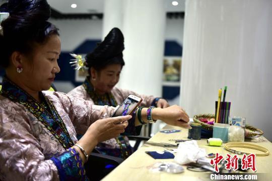 8月28日,在贵州省从江县丙妹镇銮里风情园大数据中心,一名苗族妇女在展示自己的手工刺绣成品。 吴德军 摄