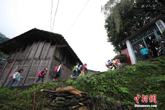 今年40岁的杨昌军是地处大山深处的贵州省丹寨县排调镇党干村教学点唯一的一名老师。新学期开学以来,每天早上杨昌军都会准时在校门口迎接一名一年级学生和7名来自不同村寨的学龄前儿童。图为9月7日,贵州省丹寨县排调镇党干村教学点,杨昌军在校门口迎接孩子们上学。 中新社发 黄晓海 摄