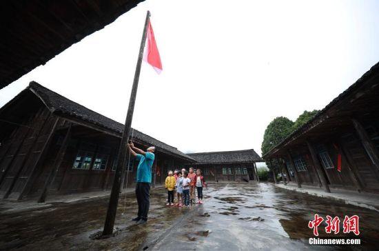 虽然只有一名适龄学生,但杨昌军还是按照标准认真地完成教学任务,每个星期排满30节课,一个人包揽了一年级所有课程。图为杨昌军(左)带着孩子们升国旗。 中新社发 黄晓海 摄