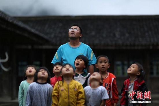 """杨昌军说:""""如果没有这个教学点,周边七八个村寨的低龄孩子们上学都要到二十多公里外的镇上,各方面都很不方便。为了让孩子们有书读,我将在教学点一直坚守下去。""""图为杨昌军与孩子们在升旗仪式上唱国歌。 中新社发 黄晓海 摄"""