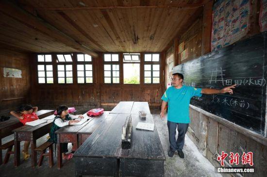 9月7日,贵州省丹寨县排调镇党干村教学点,杨昌军给一年级学生王芳英(中)上语文课,他6岁的女儿(左)在旁听。 中新社发 黄晓海 摄