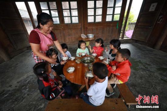 9月7日,贵州省丹寨县排调镇党干村教学点,杨昌军的妻子李丽给孩子们盛饭。 中新社发 黄晓海 摄