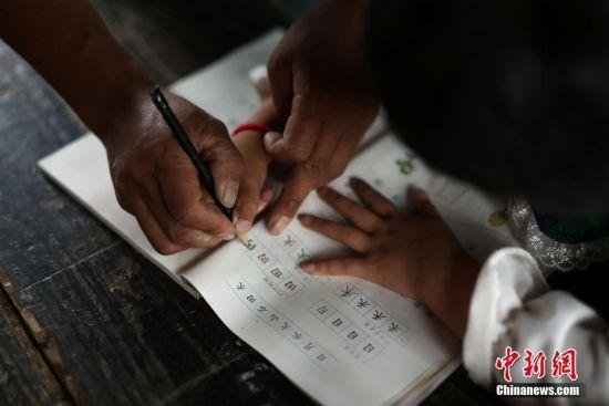 杨昌军辅导一年级学生王芳英写作业。 中新社发 黄晓海 摄