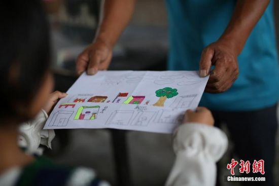 一年级学生王芳英送给杨昌军教师节礼物。 中新社发 黄晓海 摄