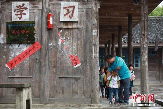 9月7日,贵州省丹寨县排调镇党干村教学点,杨昌军在放学前帮孩子们整理书包。 中新社发 黄晓海 摄