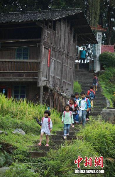杨昌军在校门口目送孩子们放学回家。 中新社发 黄晓海 摄