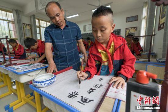 教师韦永亮教学生写水书。 中新社记者 贺俊怡 摄