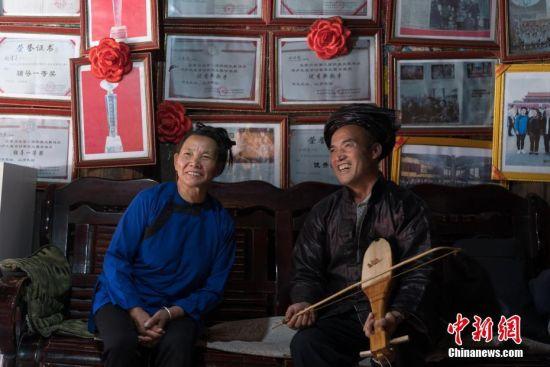 如今,现年63岁的胡官美仍然在侗寨里教歌、传歌,她表示自己要承担起传承人的责任,让侗族大歌一代一代传承下去。图为9月13日,午饭后,胡官美与丈夫杨胜锦在堂屋里为客人演唱牛腿琴歌。 中新社记者 贺俊怡 摄