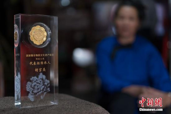 9月13日,贵州宰荡侗寨,胡官美看着颁发给她的国家级非物质文化遗产项目侗族大歌代表性传承人奖杯。 中新社记者 贺俊怡 摄