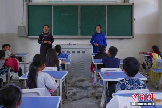 9月13日,贵州宰荡村加所小学,胡官美和女儿杨秀珠(左)给三年级的学生上音乐课,胡官美受聘每周到学校教孩子们两节侗族大歌课。 中新社记者 贺俊怡 摄