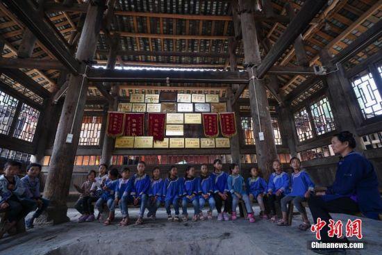 9月13日,贵州宰荡侗寨,侗族女歌师胡官美在鼓楼里给孩子们传授侗族大歌。 中新社记者 贺俊怡 摄