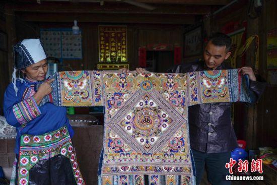 9月12日,贵州榕江平永镇乔亥村,苗族妇女龚循凤与儿子展示一件价值五万元的百鸟衣,这件百鸟衣龚循凤老人花两年的时间才制作完成。 中新社记者 贺俊怡 摄