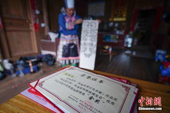 9月12日,贵州榕江平永镇乔亥村,苗族妇女龚循凤家里展示她获得的荣誉证书。 中新社记者 贺俊怡 摄