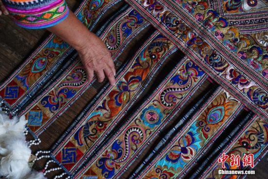 苗族妇女龚循凤介绍制作完成的百鸟衣裙摆刺绣。 中新社记者 贺俊怡 摄