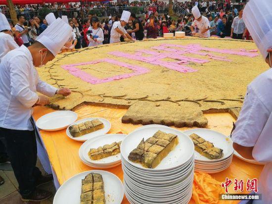 图为厨师将巨型月饼分盘。贺春雨 摄