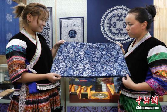 9月25日,苗族手工艺人杨颖(左)和杨熹在展示蜡染披肩。贵州省毕节市织金县苗族蜡染工艺独特,部分蜡染作品已走出大山、走出国门。中新社记者 瞿宏伦 摄