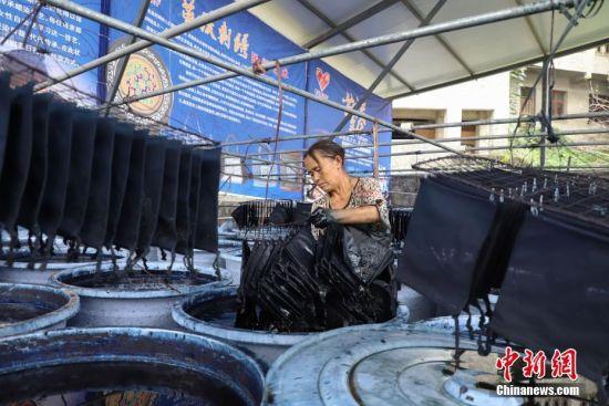 9月25日,织金县官寨乡苗族民众在染制收纳包。贵州省毕节市织金县苗族蜡染工艺独特,部分蜡染作品已走出大山、走出国门。中新社记者 瞿宏伦 摄