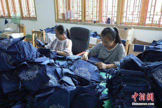9月25日,蜡染工厂的员工在进行蜡染产品的核验工作。贵州省毕节市织金县苗族蜡染工艺独特,部分蜡染作品已走出大山、走出国门。中新社记者 瞿宏伦 摄
