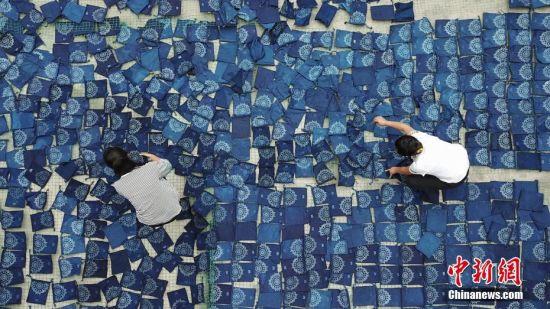 9月25日,航拍织金县官寨乡苗族民众在晾晒蜡染收纳包。贵州省毕节市织金县苗族蜡染工艺独特,部分蜡染作品已走出大山、走出国门。中新社记者 瞿宏伦 摄