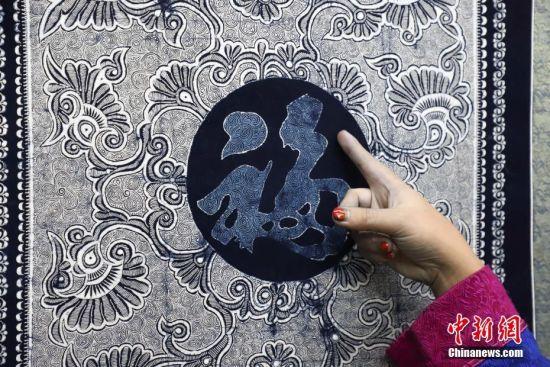 9月25日,苗族手工艺人杨琴琴在介绍《福》字蜡染作品。贵州省毕节市织金县苗族蜡染工艺独特,部分蜡染作品已走出大山、走出国门。中新社记者 瞿宏伦 摄