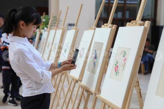 """9月29日,参观者在拍摄学生的苗绣作品。当日,贵州民族民间手工艺体验系列活动在贵州美术馆举办。来自贵阳市五所中学的百余名中学生在老师的指导下进行非遗""""苗绣""""作品创作。"""