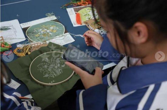 """9月29日,一名女中学生用手机拍摄自己的作品。当日,贵州民族民间手工艺体验系列活动在贵州美术馆举办。来自贵阳市五所中学的百余名中学生正在老师的指导下进行非遗""""苗绣""""作品创作。"""