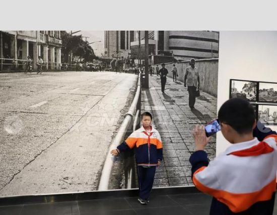 """9月29日,一名小学生在大幅照片前留影。当日,《影像见证一座古城的历史变迁――纪念改革开放四十周年》陈刚摄影展在贵州美术馆持续展出,200幅以贵阳""""人""""精神面貌的变化为主题和贵阳新旧面貌对比的作品吸引众多民众参观。"""