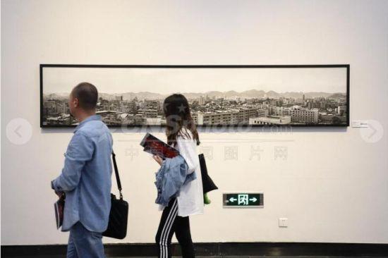 """9月29日,两位参观者从展出的老照片前走过。当日,《影像见证一座古城的历史变迁――纪念改革开放四十周年》陈刚摄影展在贵州美术馆持续展出,200幅以贵阳""""人""""精神面貌的变化为主题和贵阳新旧面貌对比的作品吸引众多民众参观。"""