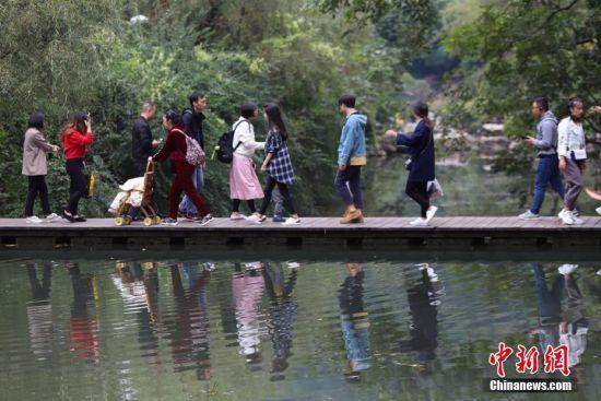 10月6月,游客行走在公园内的木栈道上。当日,是国庆黄金周第六天,假期临近结束,贵州省贵阳市黔灵山公园游客依然络绎不绝。中新社记者 瞿宏伦 摄