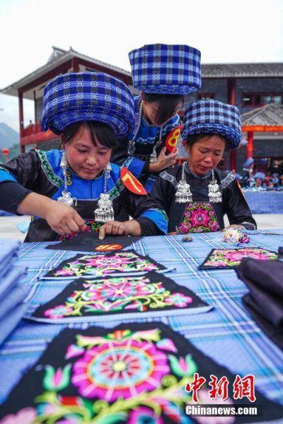 三名布依族绣娘在比赛中刺绣。中新社记者 贺俊怡 摄