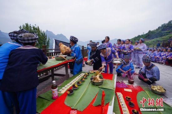 10月3日,贵州望谟桑郎镇,布依族老人在祭坛上摆放贡品,进行祭山仪式。中新社记者 贺俊怡 摄