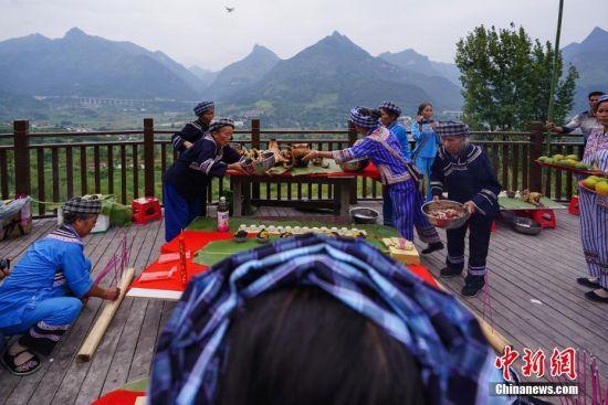 布依族老人在祭坛上摆放贡品,举行祭山仪式。中新社记者 贺俊怡 摄