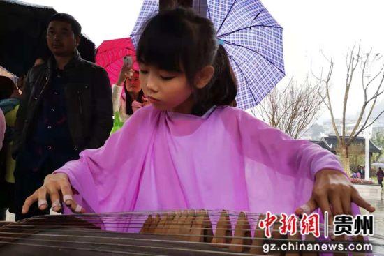 10月13日,德江县白果沱湿地公园旅游文化展示活动中,当地少儿为游客弹奏古筝。