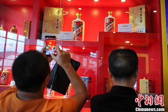 市民在茅台酒展台前用手机拍摄展出的茅台酒瓶。(资料图) 中新社记者 贺俊怡 摄
