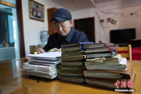 11月27日,金方隆的19本家庭日记和12本记账本。贵州省贵阳市79岁的老人金方隆,从1978年开始坚持用日记和记账本方式记录生活中的所见所闻。至今他已经写了19本家庭日记和12本记账本,记录了40年的生活变化。中新社记者 瞿宏伦 摄