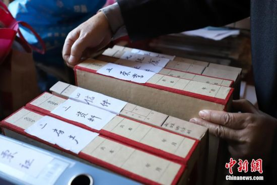 11月27日,金方隆在整理编号的档案盒。贵州省贵阳市79岁的老人金方隆,从1978年开始坚持用日记和记账本方式记录生活中的所见所闻。至今他已经写了19本家庭日记和12本记账本,记录了40年的生活变化。中新社记者 瞿宏伦 摄