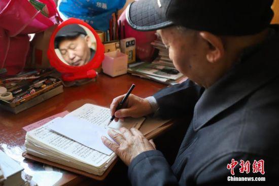 11月27日,金方隆在记录。贵州省贵阳市79岁的老人金方隆,从1978年开始坚持用日记和记账本方式记录生活中的所见所闻。至今他已经写了19本家庭日记和12本记账本,记录了40年的生活变化。中新社记者 瞿宏伦 摄